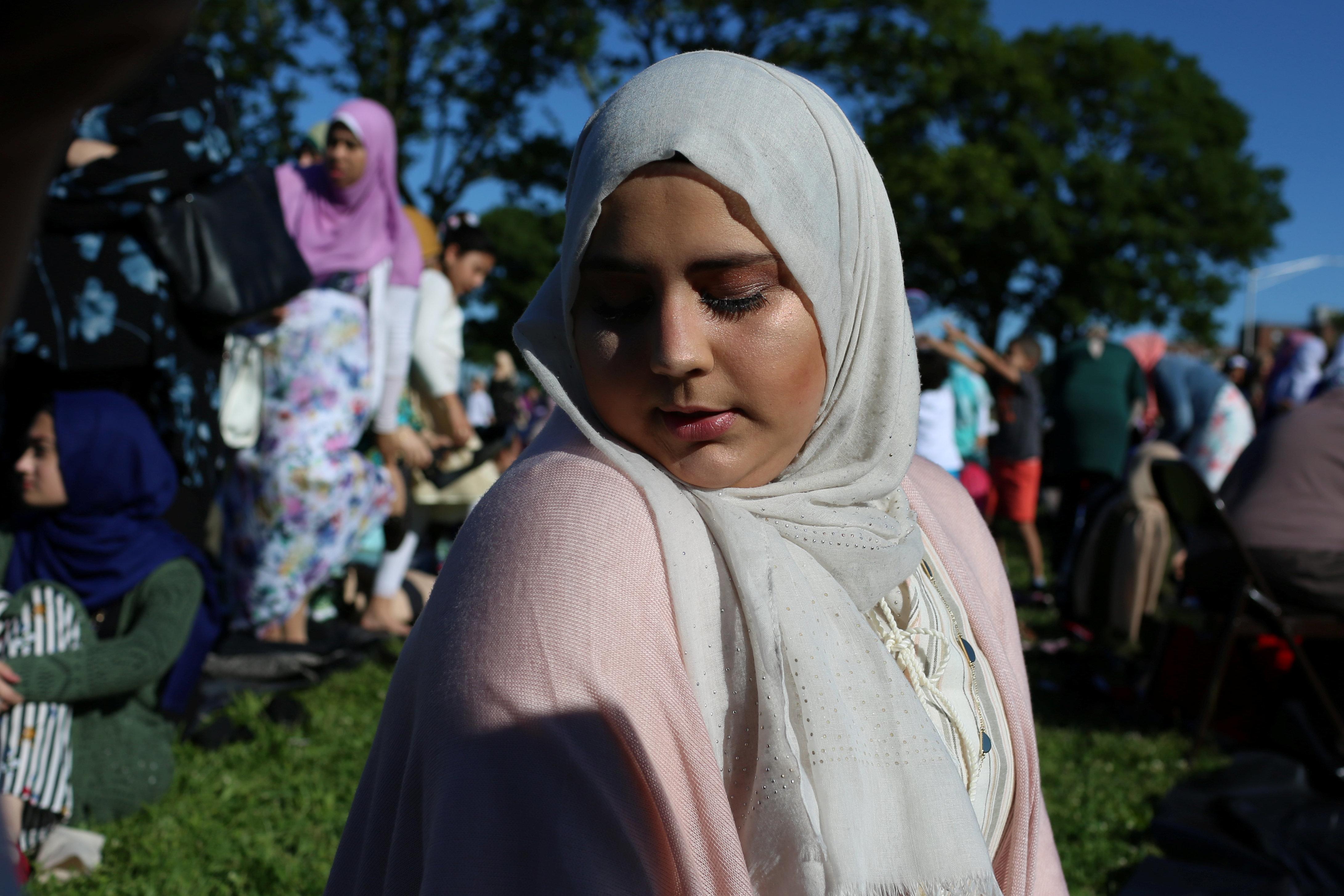 A Muslim woman prays at Bensonhurst Park to celebrate Eid Al-Fitr in the Brooklyn, New York, U.S., June 15, 2018. REUTERS/Gabriela Bhaskar
