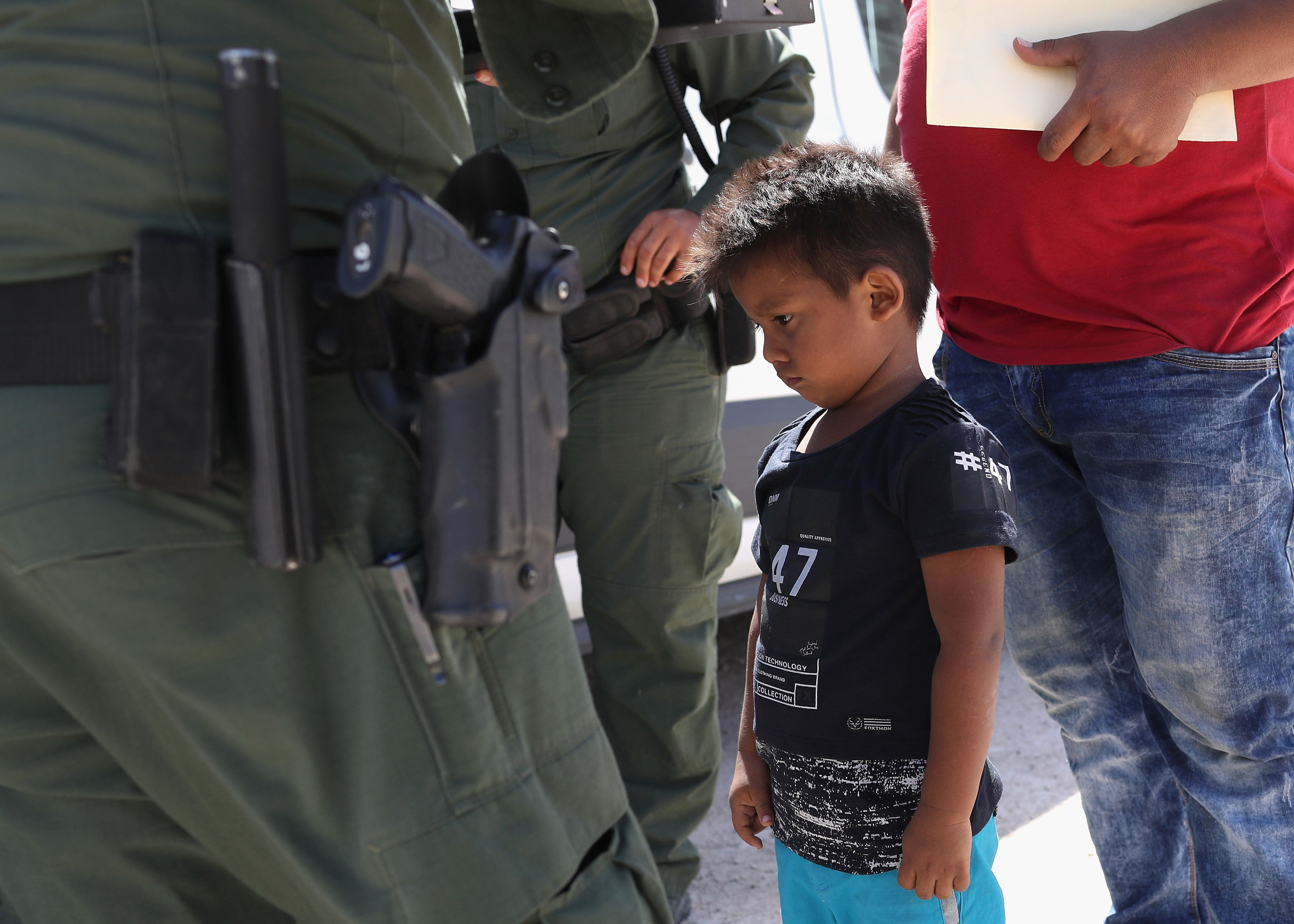 MISSION, TX - JUNE 12:  A boy and father from Honduras are taken into custody by U.S. Border Patrol agents near the U.S.-Mexico Border on June 12, 2018 near Mission, Texas. The asylum seekers were then sent to a U.S. Customs and Border Protection (CBP) processing center for possible separation. U.S. border authorities are executing the Trump administration's 'zero tolerance' policy towards undocumented immigrants. U.S. Attorney General Jeff Sessions also said that domestic and gang violence in immigrants' country of origin would no longer qualify them for political asylum status.  (Photo by John Moore/Getty Images)