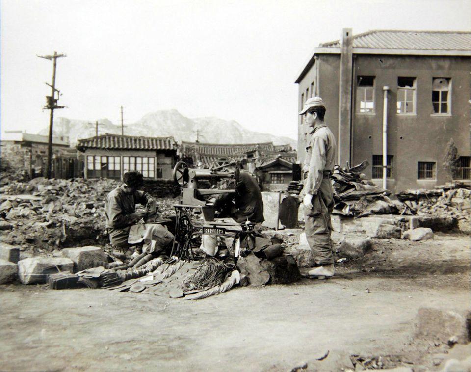 1950년 10월 28일 서울 수복 후, 한 수선공이 자기 가게가 있던 자리에서 다시 영업을 하며 전투화를 수선하는