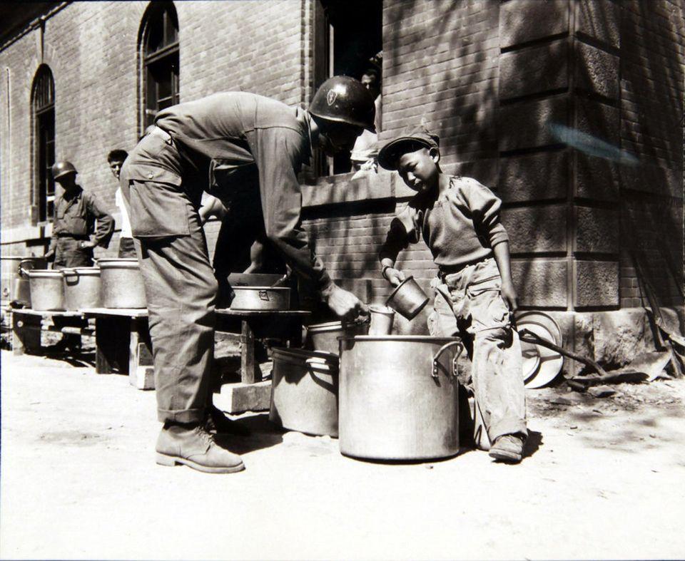 1950년 9월 23일 미군 부대에서 한 소년이 미군에게 커피를 퍼주고 있는 모습. 전쟁으로 부모를 잃은 고아 중 일부는 '부대 마스코트(unit mascot)'라고 하여,...