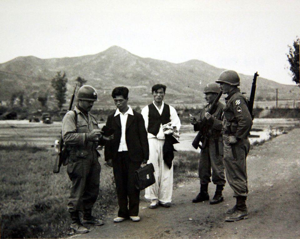 1950년 10월 15일 미군 병사가 민간인의 신분을 확인하기 위해 신분증을 살피고 있는
