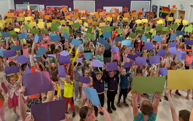 Children atDownfield Primary Schoolhold up coloured card to make a 400-person rainbow