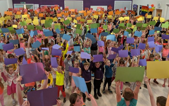 """Children at&nbsp;<a href=""""https://www.dundeecity.gov.uk/service-area/children-and-families-service/education/downfield-primary-school"""" target=""""_blank"""">Downfield Primary School</a>&nbsp;hold up coloured card to make a 400-person rainbow flag."""