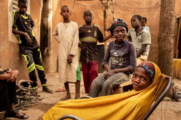 Ramatou (yellow veil), 12, and Daoussiya (in cap), 7, unaccompanied minors who are being returned to...