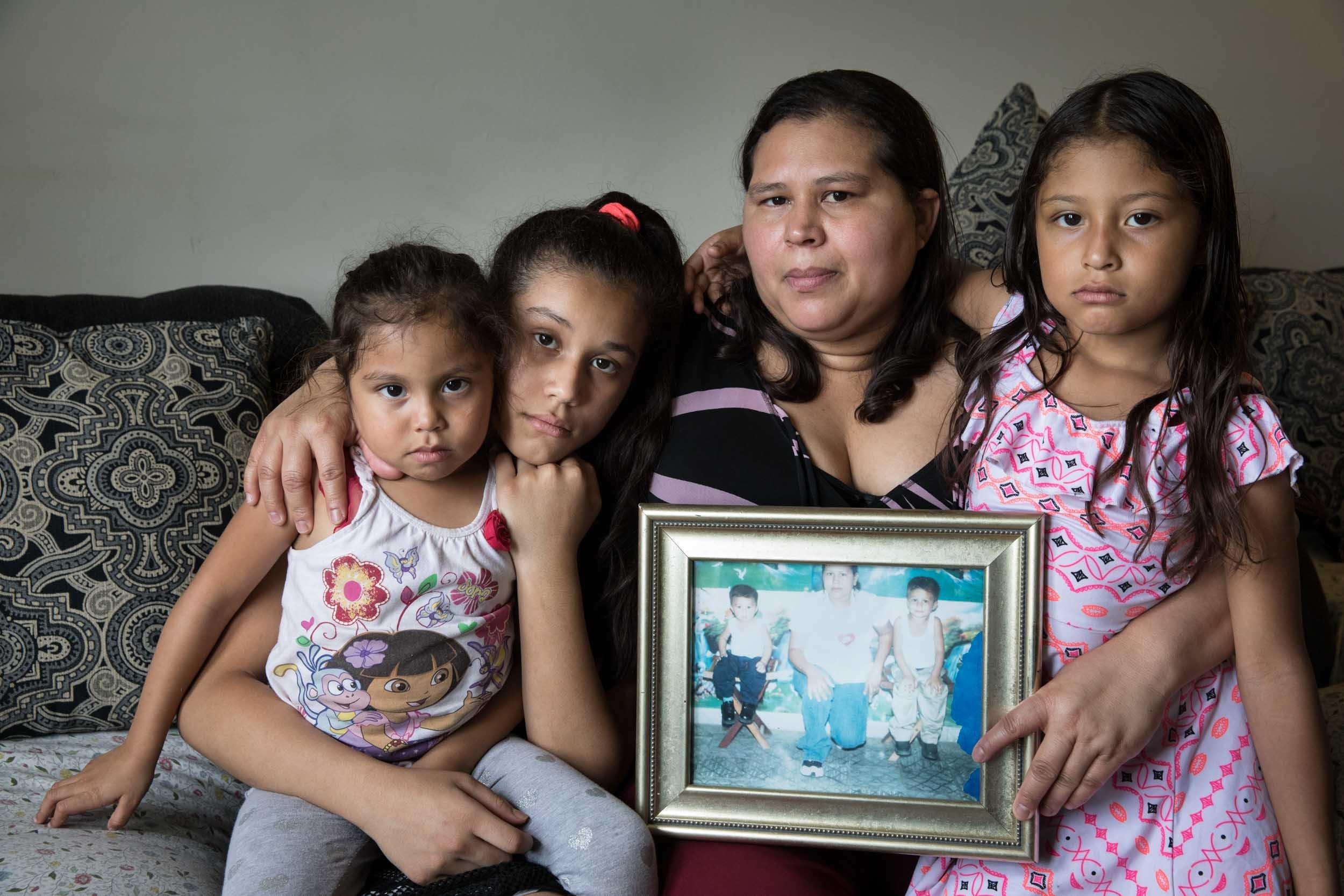 Aracely con sus tres hijas, Alyson (4 años), Emely (11) y Gabriela (7). Sostiene una fotografía de sus...