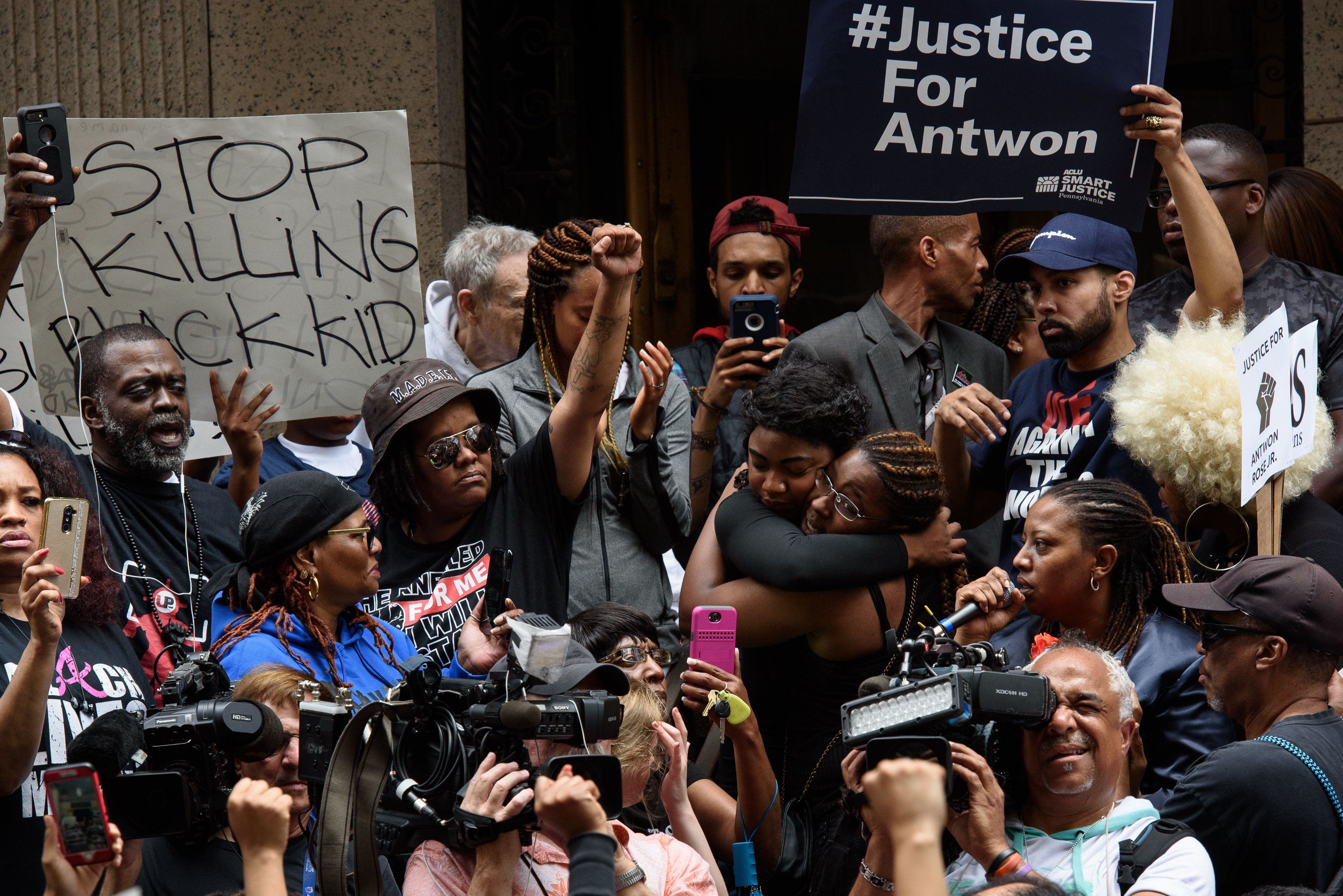 PITTSBURGH, PA - JUNE 21: Protestors embrace as more than 200 people gathered for a rally to protest the fatal shooting of an unarmed black teen at the Allegheny County Courthouse on June 21, 2018 in Pittsburgh, Pennsylvania. The rally comes in the aftermath of the fatal shooting of Antwon Rose by an East Pittsburgh police officer Tuesday night as the 17-year-old ran after being stopped by police in a vehicle suspected of being involved in an earlier shooting. The organizers called on Allegheny County District Attorney Stephen Zappala Jr. to bring criminal charges against the officer.  (Photo by Justin Merriman/Getty Images)