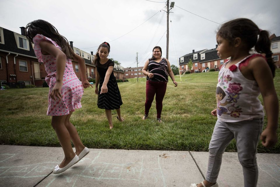 Aracely observa cómo juegan sus hijas en el barrio de Baltimore en el que