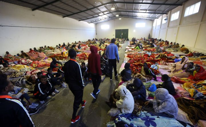 A picture taken on Dec. 11, 2017, shows African migrants sitting in a shelter at the Tariq Al-Matar migrant detention center