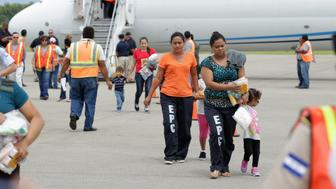 Women and their children walk on the tarmac after being deported from the U.S., at the Ramon Villeda international airport in San Pedro Sula, in this July 14, 2014 handout provided by the Honduran Presidential House. The U.S. deported a group of Honduran children on Monday in the first flight since President Barack Obama pledged to speed up the process of sending back illegal immigrant children from Central America. Monday's charter flight from New Mexico to San Pedro Sula, the city with the highest murder rate in the world, deported 17 Honduran adult women, as well as 12 girls and nine boys, aged between 18 months and 15 years, the Honduran government said. REUTERS/Presidential House/Handout via Reuters (HONDURAS - Tags: POLITICS SOCIETY IMMIGRATION) ATTENTION EDITORS - THIS PICTURE WAS PROVIDED BY A THIRD PARTY. REUTERS IS UNABLE TO INDEPENDENTLY VERIFY THE AUTHENTICITY, CONTENT, LOCATION OR DATE OF THIS IMAGE. FOR EDITORIAL USE ONLY. NOT FOR SALE FOR MARKETING OR ADVERTISING CAMPAIGNS. THIS PICTURE IS DISTRIBUTED EXACTLY AS RECEIVED BY REUTERS, AS A SERVICE TO CLIENTS
