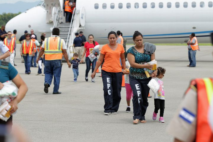 Women and their children walk on the tarmac at the Ramon Villeda international airport in San Pedro Sula, Honduras, after bei