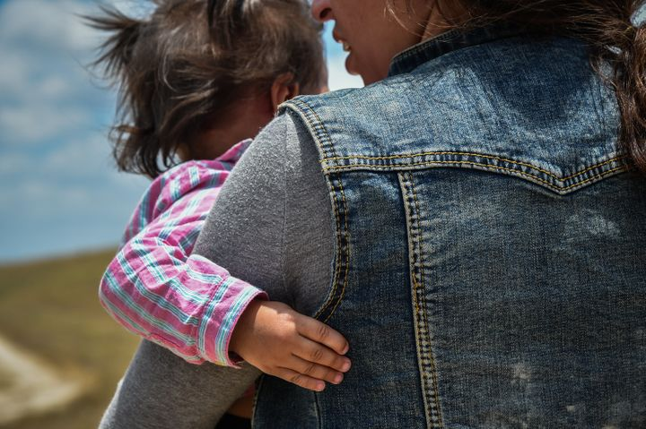 MCALLEN, TX - JUNE 29: Karina Lopez, a 23-year-old single mother from Guatemala carries her one-year-old daughter in her arms