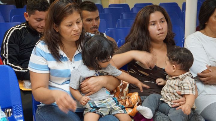 Mothers and children wait to be assisted by volunteers in a humanitarian center in the border town of McAllen, Texas, on June