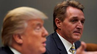 U.S. President Donald Trump, flanked by U.S. Senator Jeff Flake, speaks to reporters prior to a lunch meeting with Senate Republicans at the White House in Washington, U.S. December 5, 2017.  REUTERS/Jonathan Ernst