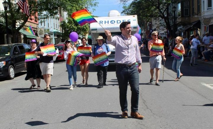 "Democrat Gareth Rhodes marches in the pride parade in Hudson, N.Y., on June 16, with his ""Rhodes Trip"" Winnebago picking"