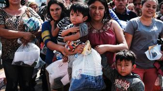MCALLEN, TX - JUNE 23: Dozens of women, men and their children, many fleeing poverty and violence in Honduras, Guatamala and El Salvador, arrive at a bus station following release from Customs and Border Protection on June 23, 2018 in McAllen, Texas. Once families and individuals are released and given a court hearing date they are brought to the Catholic Charities Humanitarian Respite Center to rest, clean up, enjoy a meal and to get guidance to their next destination. Before President Donald Trump signed an executive order Wednesday that halts the practice of separating families who are seeking asylum, over 2,300 immigrant children had been separated from their parents in the zero-tolerance policy for border crossers (Photo by Spencer Platt/Getty Images)