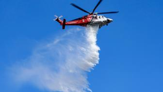 A firefighting helicopter makes a water drop over a brush fire in Burbank, California on May 25, 2018. (Photo by Ronen Tivony/NurPhoto via Getty Images)