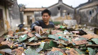 GUIYU, CHINA - MARCH 26:  A worker sorts through stripped computer boards March 26, 2008 in Guiyu, China. Since the late 1980's, e-waste from developed countries has been imported to China and broken down at Guiyu. The city comprises 21 villages with 5,500 family workshops handling e-waste. According to the local government Web site, city businesses process 1.5 million tons of e-waste a year, pulling in $75 million in revenue. As much as 80 percent of it comes from overseas.  (Photo by Jim Xu/Getty Images)