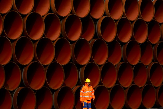 A worker stands in front of pipes which lie stacked at the Nord Stream 2 facility on Ruegen Island, Germany,...