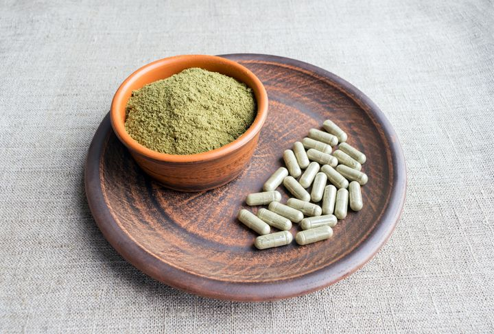Kratom powder is seen next to capsules containing the herbal supplement.