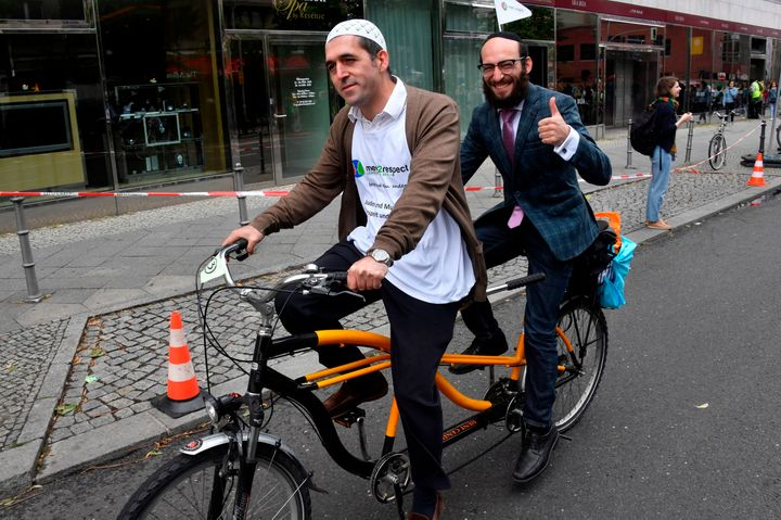 Imam Osman Oers (front) and Rabbi Akiva Weingarten participate in an interfaith bicycleride in Berlin on June 24, 2018.