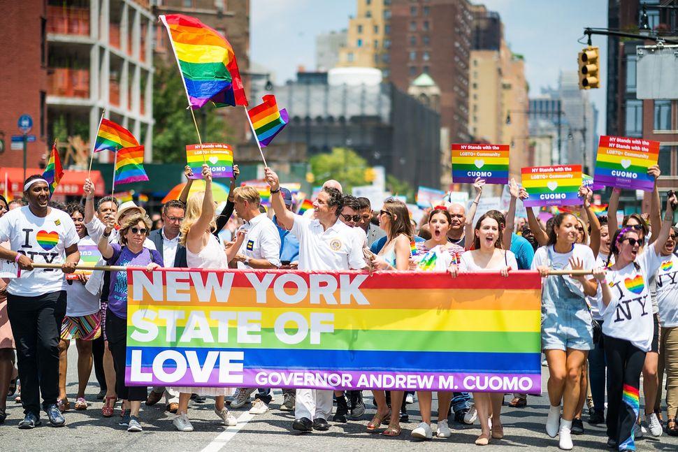 New York Gov. Andrew Cuomo (center) and hispartner Sandra Lee (left with flag) attend the 2018 New York City Pride Marc