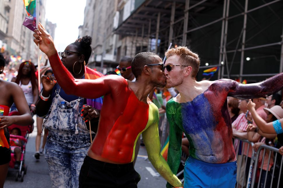 People kiss as they participate in the Pride parade.