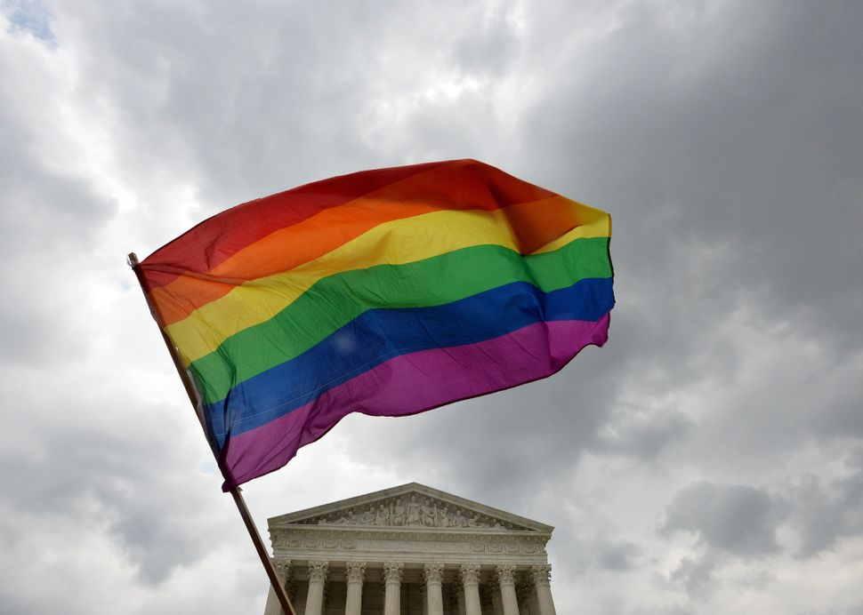 The multicolored flag of the gay rights movement was waved triumphantly outside the Supreme Court building in Washington afte