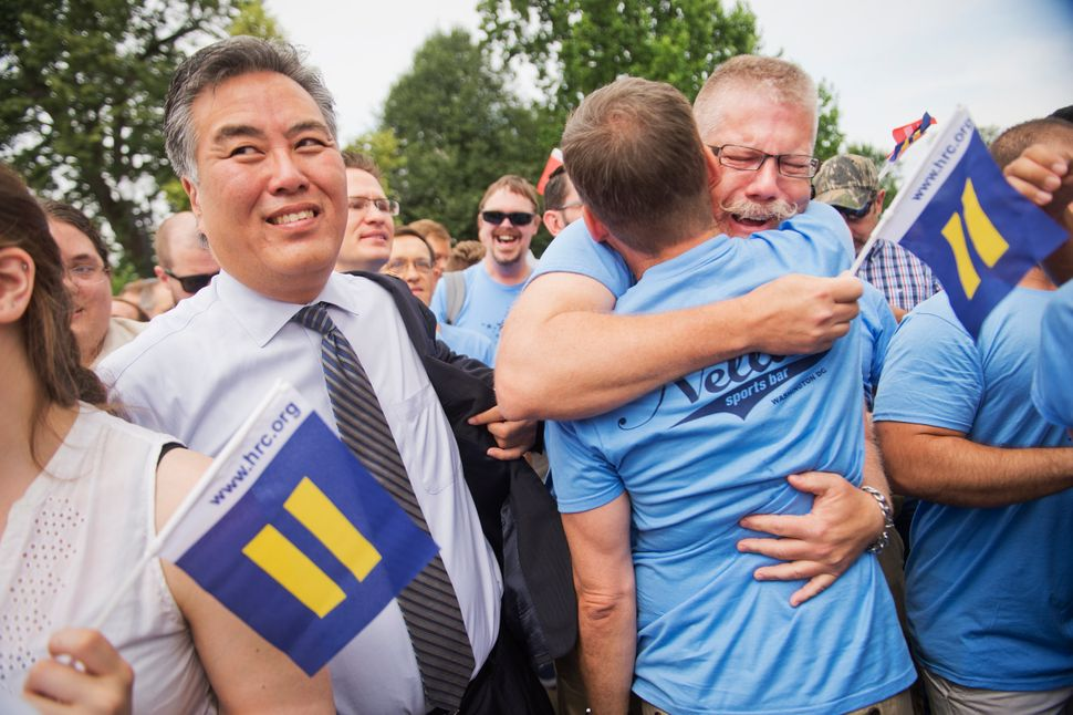 Mark Uhen, in glasses, hugged Bill Cutter as Rep. Mark Takano (D-Calif.) stood with them outside the Supreme Court building.