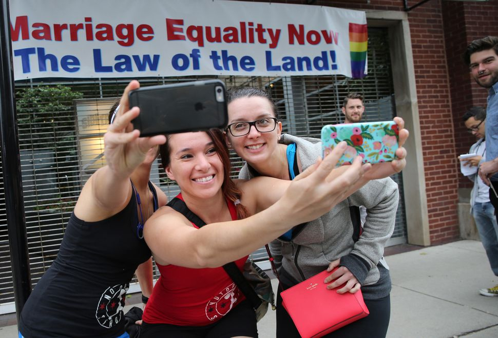 Christie Jones, Teresa Moreno and Michelle Gregory (left to right) posed for selfies in front of a banner in Chicago proclaim