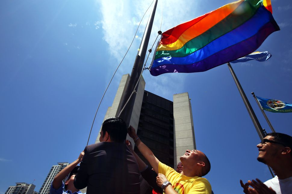 Long Beach Mayor Robert Garcia (with his back to the camera) was helped by Mark Magdaleno as they raised a rainbow Pride Flag