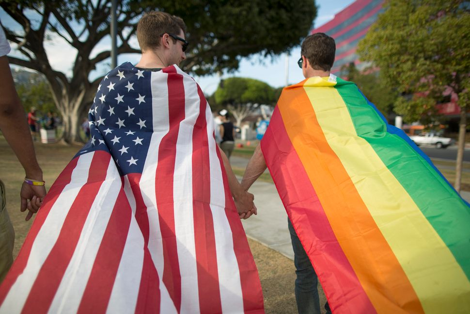 Robert Oliver (left) and Mark Heller held hands, their bodies draped in flags, as they celebrated in West Hollywood, Cal