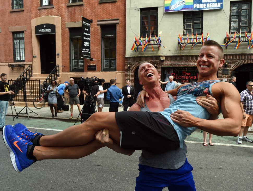 Justin Kattler ecstatically hoisted his partner, Tim Loecker, outside the famed Stonewall Tavern in New York. The two we