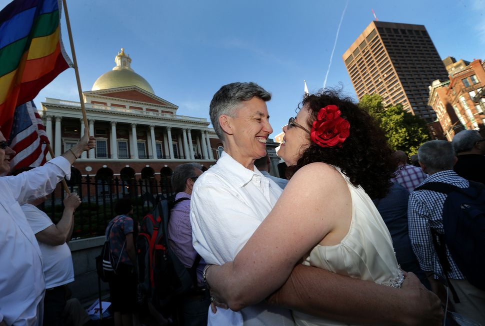 Sandy Bailey (left) and wife Liz Nania hold one another on the steps of the Massachusetts State House in Boston. Massachusett