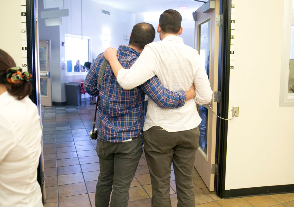 Mike Gomez (right) and Michael Carter pose for a photo after receiving their marriage license at the Travis County Clerk's of
