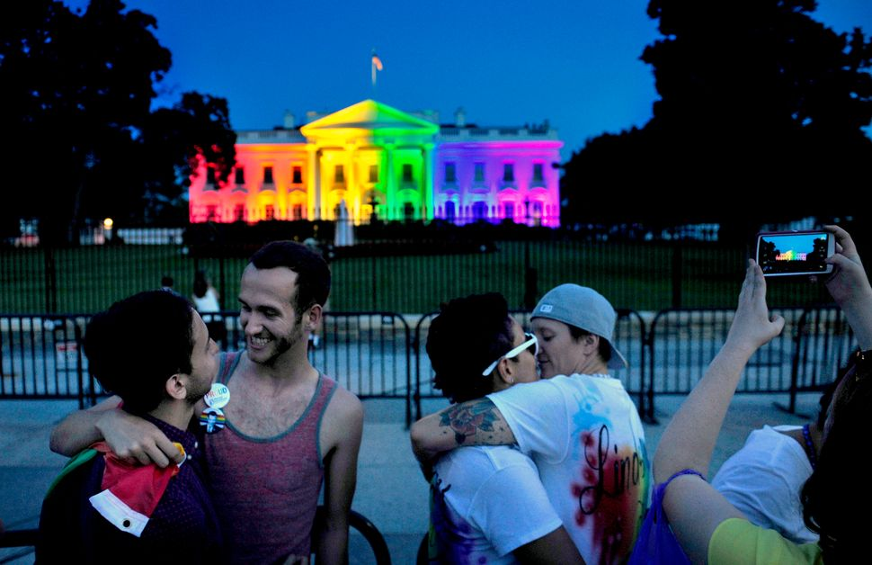 With the White House bathed in gay pride colors, two couples embraced in front of it.