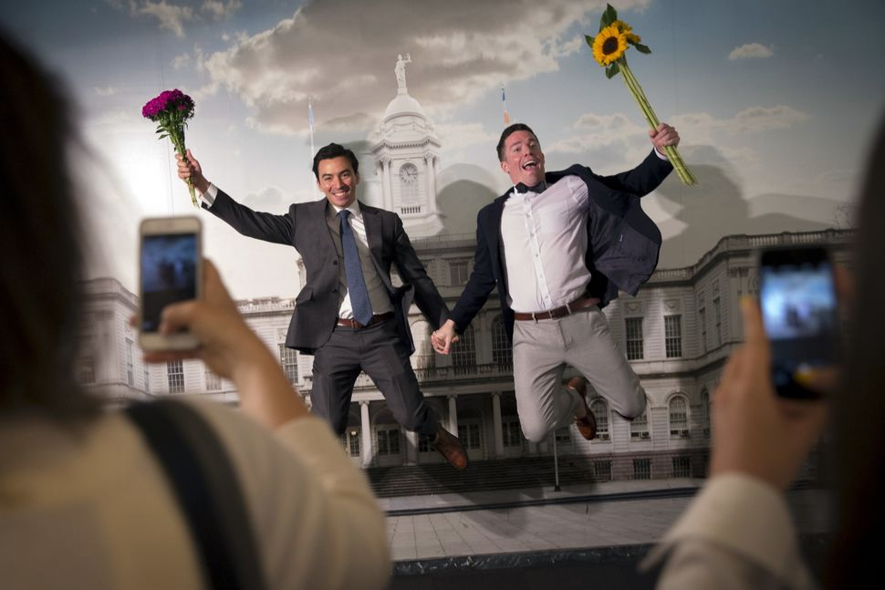 Rodrigo Zamora (left) and Ashby Hardesty jump for joy after their wedding in New York that coincided with the court decision.