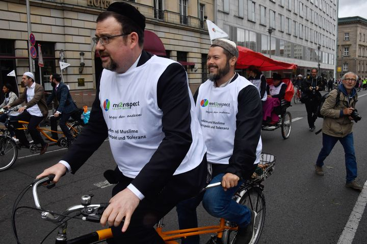 Imam Ender Cetin (back) and Rabbi Elias Dray (front) bike together in Berlin on June 24, 2018.