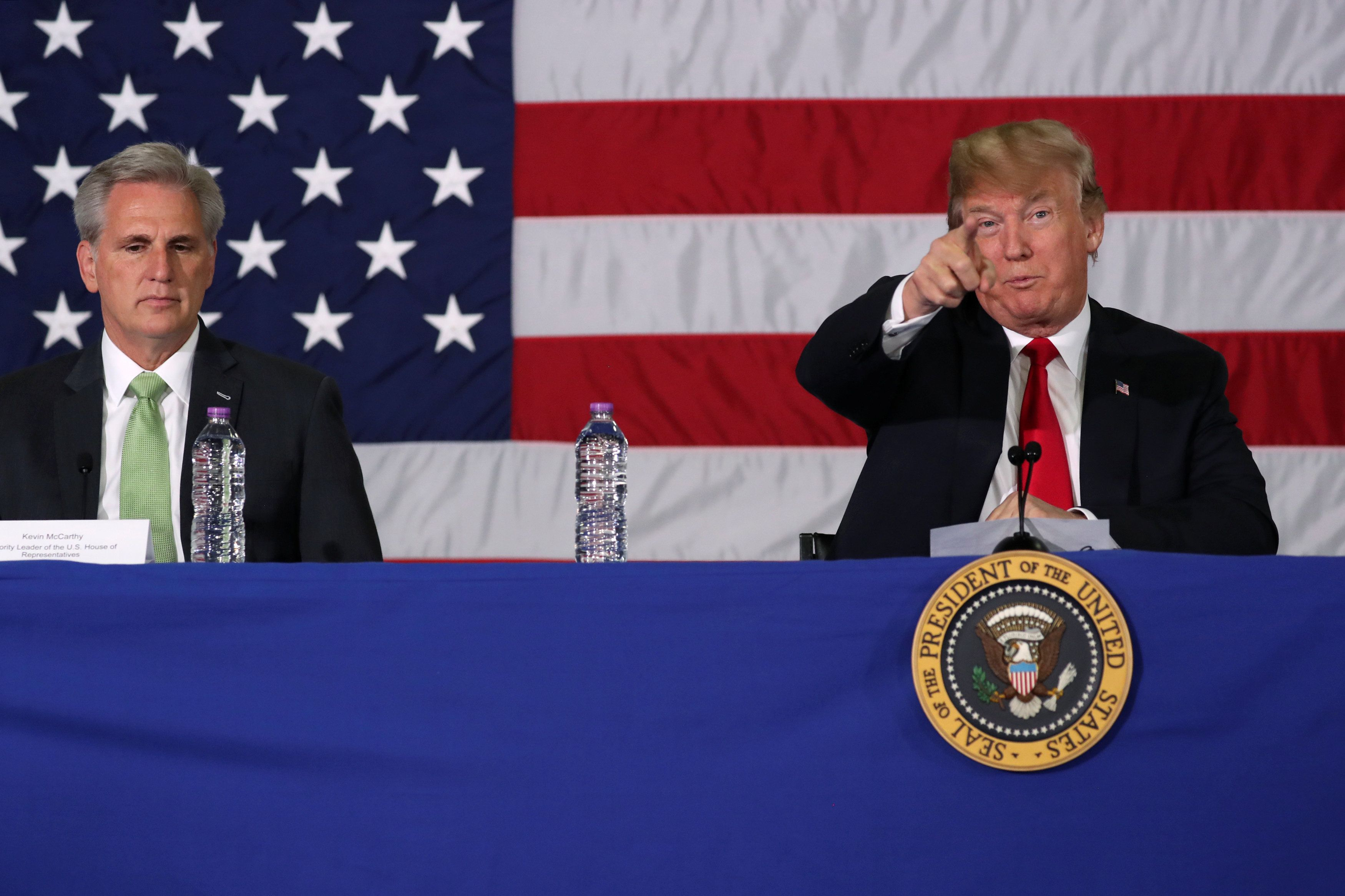 U.S. President Donald Trump, flanked by House Majority Leader Kevin McCarthy (R-CA), calls out reporters at the back of the room as he participates in a roundtable discussion about trade in Duluth, Minnesota, U.S. June 20, 2018. REUTERS/Jonathan Ernst