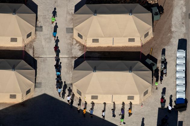 Immigrant children are led in single file between tents at a detention facility next to the Mexican border...
