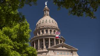 An American flag flies with the Texas state flag outside the Texas State Capitol building in Austin, Texas, U.S., on Wednesday, March 15, 2017. Austin has spent the last 10 months engaged in a big experiment in urban transportation. Several hundreds of thousands of people will descend upon Austin for the annual South by Southwest festival, a nine-day event that could be described as a tech conference, a music and film festival. Photographer: David Paul Morris/Bloomberg via Getty Images