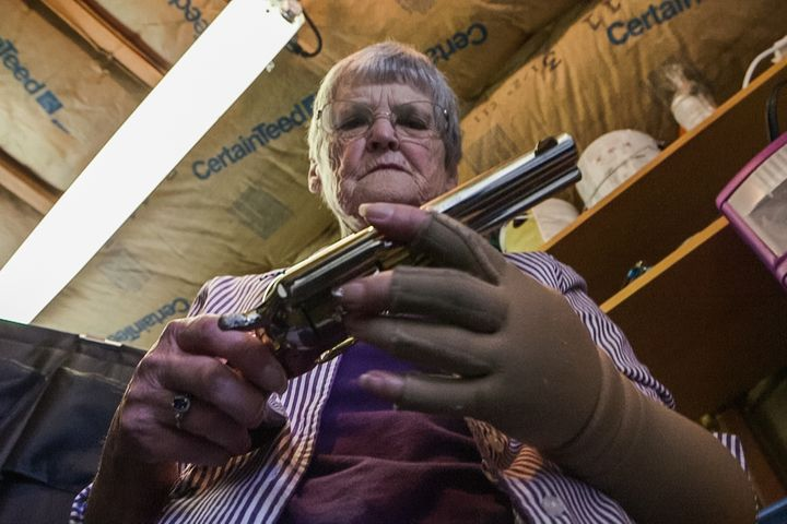 Dee Hill examines the last of the guns that once belonged to her husband, Darrell.