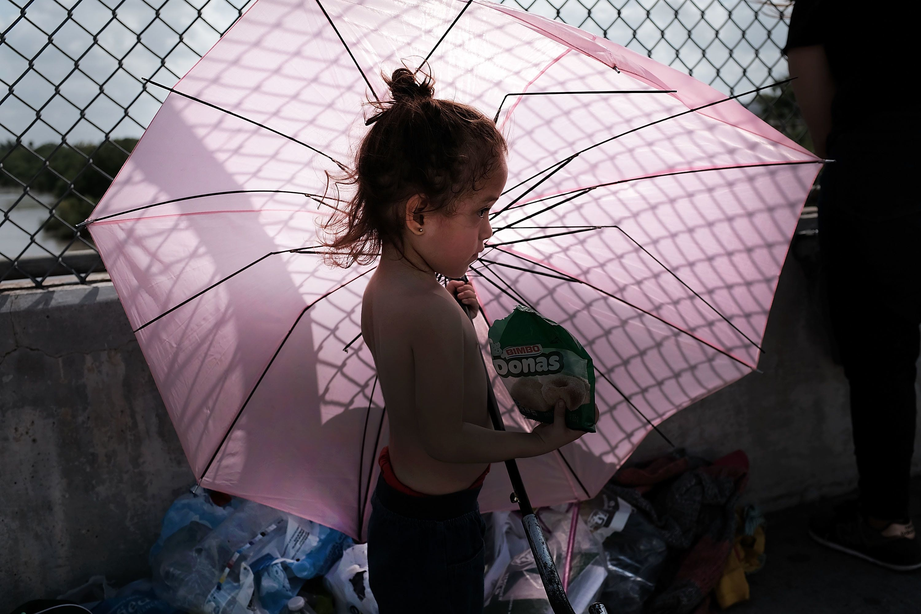 A Honduran child stands in the shade of an umbrella as she waits with her mother along the border bridge after being denied e