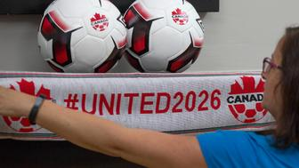 An employee holds up a scarf with the hashtag for World Cup in 2026 at Soccer Canada Headquarters in Ottawa, Ontario on June 13, 2018, as Canada will co-host the 2026 World Cup with Mexico and the US. - The 2026 World Cup hosted by Canada, Mexico and the United States will be 'a great tournament,' Canadian Prime Minister Justin Trudeau said Wednesday, setting aside a simmering trade dispute with Washington. 'Good news this morning: The 2026 FIFA World Cup is coming to Canada, the US and Mexico,' the prime minister said in a Twitter message. 'Congratulations to everyone who worked hard on this bid - it's going to be a great tournament!' (Photo by Lars Hagberg / AFP)        (Photo credit should read LARS HAGBERG/AFP/Getty Images)