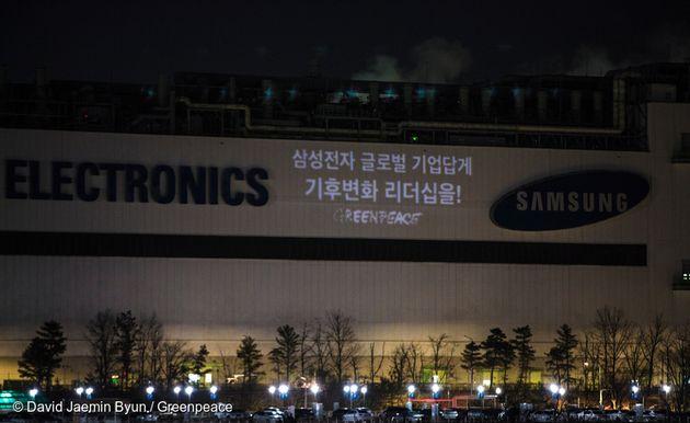 지난 2월 그린피스 서울사무소 활동가들이 삼성전자 기흥 반도체 공장에 100% 재생가능에너지 사용을 요구하는 문구를 프로젝터로 쏘고