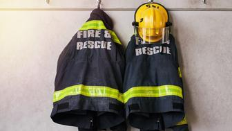 Cropped shot of firemen's clothing hanging from a wall