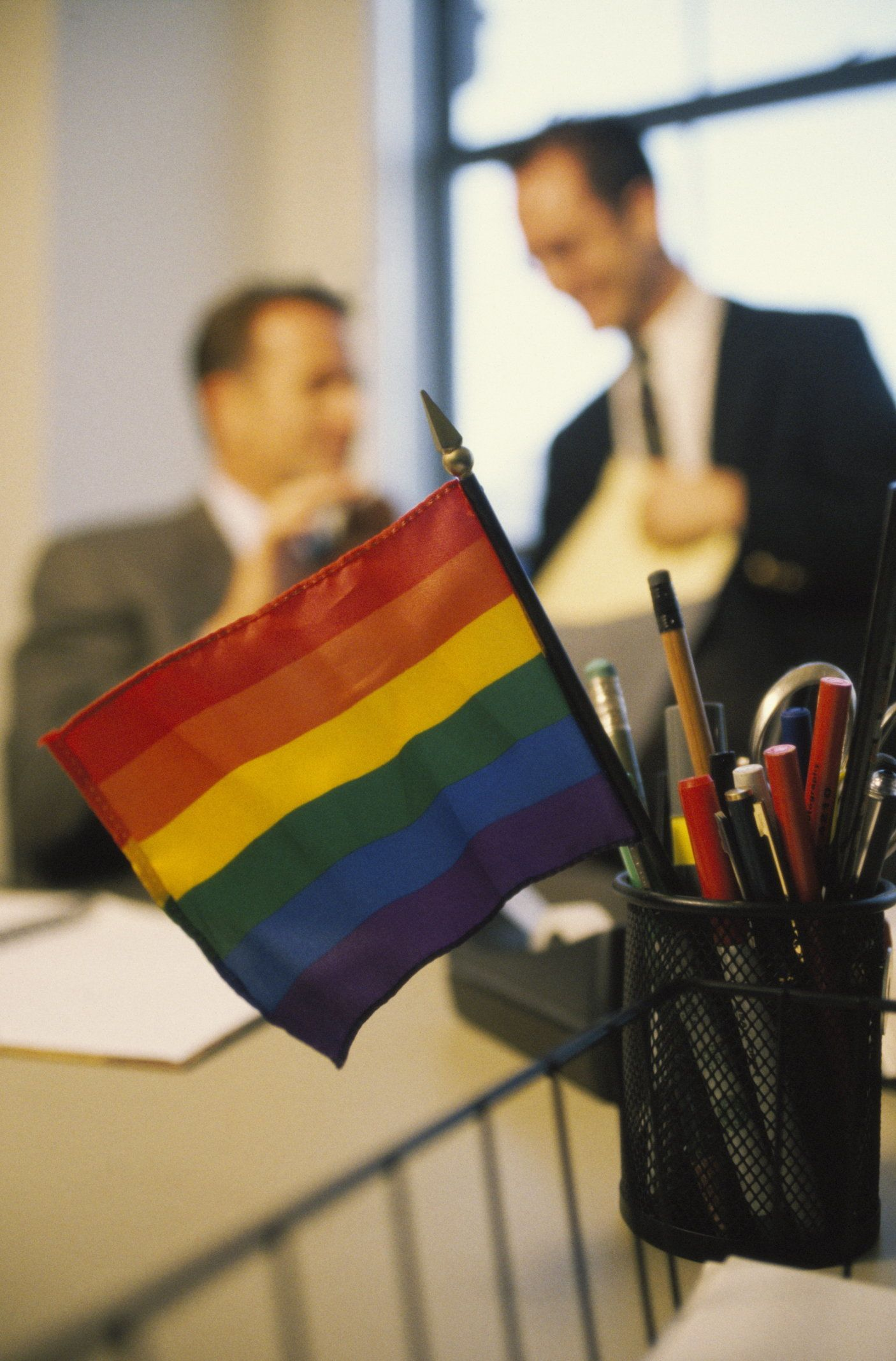 Rainbow flag in pencil holder on office desk