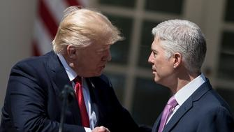 Neil Gorsuch (R) shakes US President Donald Trump's hand after taking the judicial oath during a ceremony in the Rose Garden of the White House April 10, 2017 in Washington, DC. / AFP PHOTO / Brendan Smialowski        (Photo credit should read BRENDAN SMIALOWSKI/AFP/Getty Images)