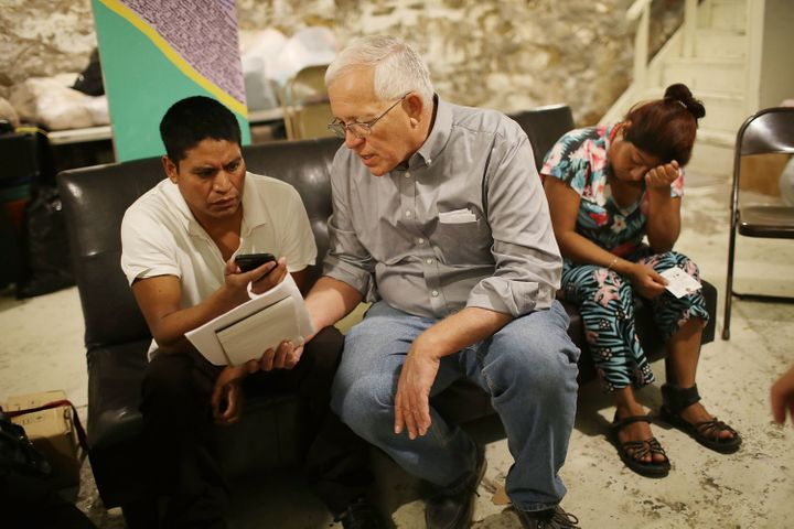 Ruben Garcia (center), director of Annunciation House, speaks on a cellphone with a person from the Office of Refugee Resettl