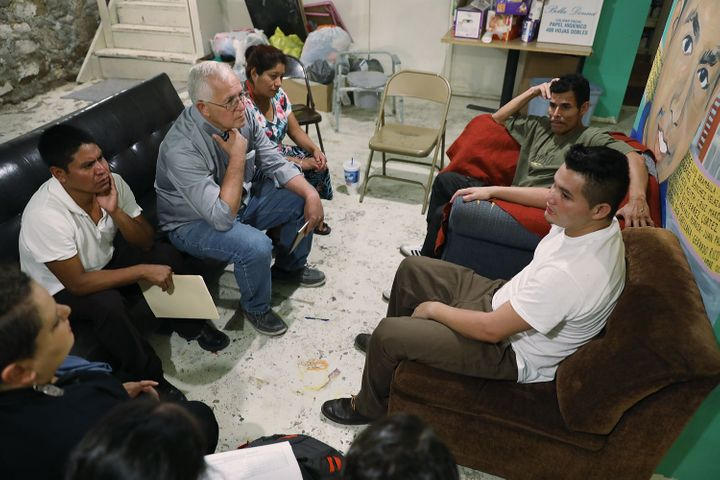 Garcia sits with migrants from Honduras and Guatemala at the Annunciation House migrant shelter.
