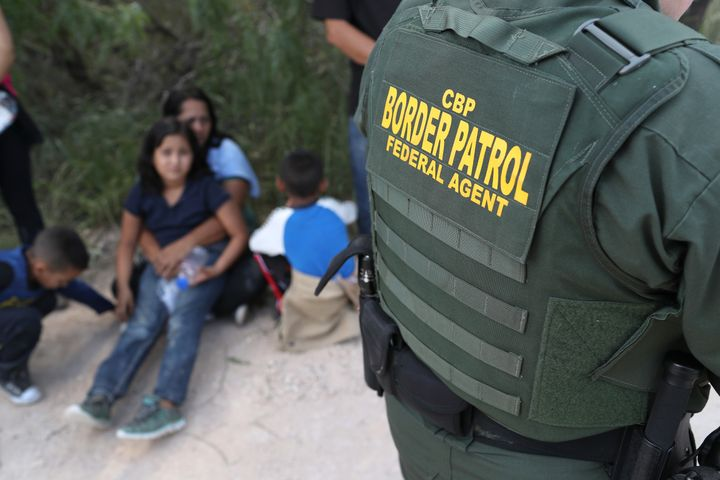 Central American asylum seekers wait as U.S. Border Patrol agents take them into custody earlier this month near McAllen, Tex